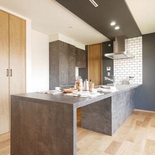 Cette image montre une cuisine ouverte linéaire asiatique avec un évier encastré, un placard à porte affleurante, des portes de placard grises, une crédence blanche, une crédence en carrelage métro, un électroménager en acier inoxydable, un sol en bois clair, une péninsule, un sol beige et un plan de travail gris.