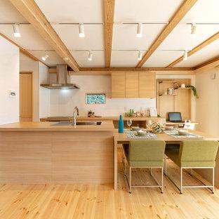 Diseño de cocina comedor de galera, asiática, con península, salpicadero blanco, electrodomésticos de acero inoxidable, fregadero encastrado, armarios con paneles lisos, puertas de armario de madera clara, encimera de madera, suelo de madera clara, suelo beige y encimeras beige