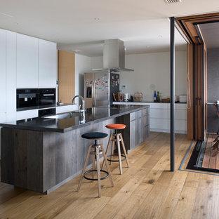 東京23区のラスティックスタイルのおしゃれなキッチン (アンダーカウンターシンク、インセット扉のキャビネット、濃色木目調キャビネット、クオーツストーンカウンター、シルバーの調理設備の、無垢フローリング、ベージュの床、黒いキッチンカウンター) の写真