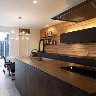 東京23区のモダンスタイルのおしゃれなキッチン (アンダーカウンターシンク、インセット扉のキャビネット、黒いキャビネット、シルバーの調理設備、セラミックタイルの床、グレーの床、黒いキッチンカウンター) の写真