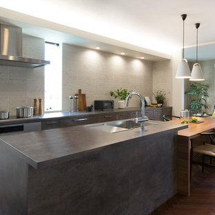 東京23区の北欧スタイルのおしゃれなキッチン (アンダーカウンターシンク、インセット扉のキャビネット、グレーのキャビネット、ベージュキッチンパネル、シルバーの調理設備、無垢フローリング、茶色い床、グレーのキッチンカウンター) の写真