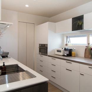 モダンスタイルのおしゃれなキッチン (アンダーカウンターシンク、インセット扉のキャビネット、濃色木目調キャビネット、白い調理設備、ベージュの床、白いキッチンカウンター) の写真