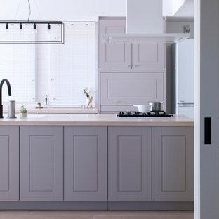 東京23区の広いトランジショナルスタイルのおしゃれなキッチン (グレーのキャビネット、白い調理設備、淡色無垢フローリング、ベージュの床、ベージュのキッチンカウンター、ドロップインシンク、レイズドパネル扉のキャビネット) の写真