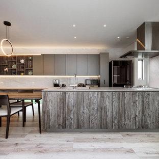 Ispirazione per una cucina moderna con lavello sottopiano, ante a filo, ante grigie, elettrodomestici in acciaio inossidabile, parquet chiaro, penisola, pavimento beige e soffitto in carta da parati