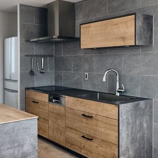 Aménagement d'une cuisine ouverte linéaire moderne avec un évier encastré, un placard à porte affleurante, des portes de placard en bois brun, une crédence grise, une crédence en carreau de céramique, un électroménager en acier inoxydable, un sol en bois clair, un îlot central, un sol beige, un plan de travail gris et un plafond en papier peint.