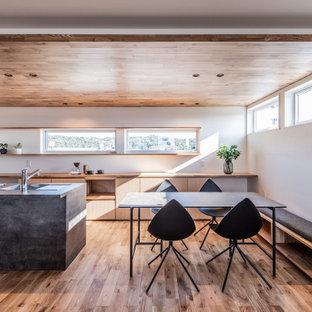 Cette photo montre une grand cuisine ouverte parallèle asiatique avec un évier encastré, un placard à porte affleurante, des portes de placard grises, une crédence grise, un électroménager en acier inoxydable, un sol en bois brun, une péninsule, un sol beige, un plan de travail gris et un plafond en papier peint.