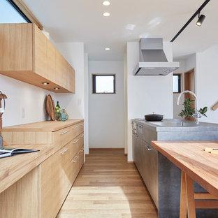 東京23区のコンテンポラリースタイルのおしゃれなキッチン (白いキッチンパネル、茶色い床、フラットパネル扉のキャビネット、淡色木目調キャビネット、木材カウンター、パネルと同色の調理設備、淡色無垢フローリング、茶色いキッチンカウンター) の写真