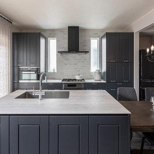 トラディショナルスタイルのおしゃれなキッチン (アンダーカウンターシンク、インセット扉のキャビネット、グレーのキャビネット、グレーのキッチンパネル、黒い調理設備、白いキッチンカウンター) の写真