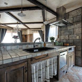 他の地域のシャビーシック調のおしゃれなキッチン (ドロップインシンク、落し込みパネル扉のキャビネット、ヴィンテージ仕上げキャビネット、タイルカウンター、テラコッタタイルの床、茶色い床) の写真