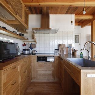他の地域のラスティックスタイルのおしゃれなキッチン (一体型シンク、落し込みパネル扉のキャビネット、中間色木目調キャビネット、ステンレスカウンター、無垢フローリング、ベージュの床、表し梁) の写真