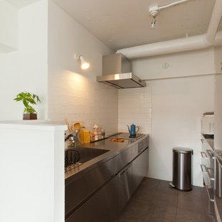 東京23区のコンテンポラリースタイルのおしゃれなII型キッチン (一体型シンク、フラットパネル扉のキャビネット、ステンレスキャビネット、ステンレスカウンター、メタリックのキッチンパネル、シルバーの調理設備の、アイランドなし) の写真