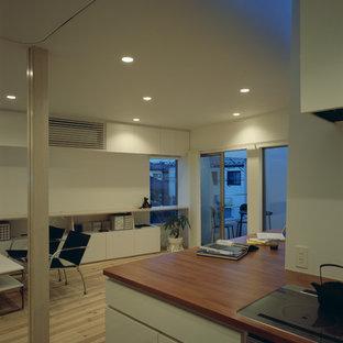 Modelo de cocina minimalista, abierta, con armarios con rebordes decorativos, puertas de armario blancas, encimera de madera, electrodomésticos de acero inoxidable, suelo de madera clara, una isla, suelo beige y encimeras rojas