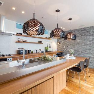 名古屋のコンテンポラリースタイルのおしゃれなキッチン (一体型シンク、フラットパネル扉のキャビネット、中間色木目調キャビネット、ステンレスカウンター、白いキッチンパネル、無垢フローリング、茶色い床、グレーのキッチンカウンター) の写真
