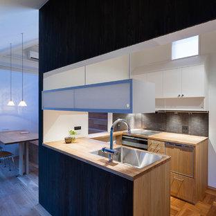 他の地域のアジアンスタイルのおしゃれなキッチン (シングルシンク、フラットパネル扉のキャビネット、中間色木目調キャビネット、木材カウンター、無垢フローリング、茶色い床) の写真