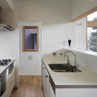 東京23区の小さいモダンスタイルのおしゃれなキッチン (アンダーカウンターシンク、フラットパネル扉のキャビネット、白いキャビネット、白いキッチンパネル、ガラス板のキッチンパネル、黒い調理設備、合板フローリング、ベージュの床、白いキッチンカウンター) の写真