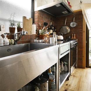 東京23区の小さいコンテンポラリースタイルのおしゃれなキッチン (一体型シンク、オープンシェルフ、ステンレスカウンター、茶色いキッチンパネル、レンガのキッチンパネル、シルバーの調理設備の、無垢フローリング、アイランドなし、ベージュの床) の写真