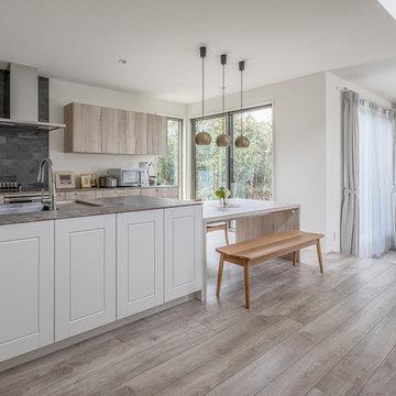縦線を基調としたモダンな框扉に粗い木目や石ような天板をコーディネートしたモダンなキッチン