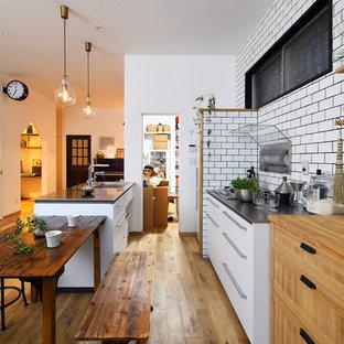 他の地域の北欧スタイルのおしゃれなキッチン (シングルシンク、フラットパネル扉のキャビネット、白いキャビネット、無垢フローリング、茶色い床) の写真