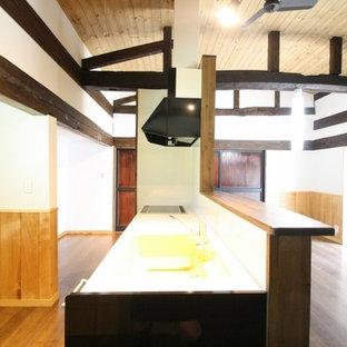 他の地域のアジアンスタイルのおしゃれなキッチン (茶色いキャビネット、人工大理石カウンター、白いキッチンパネル、白い調理設備、茶色い床、アンダーカウンターシンク、インセット扉のキャビネット、無垢フローリング) の写真