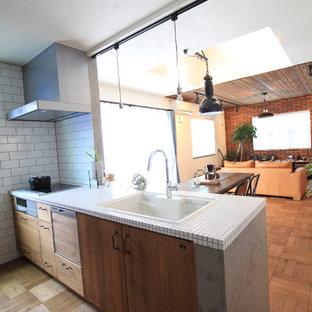 他の地域のアジアンスタイルのおしゃれなキッチン (ドロップインシンク、フラットパネル扉のキャビネット、中間色木目調キャビネット、タイルカウンター、無垢フローリング、茶色い床) の写真