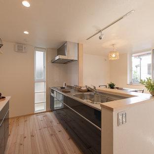 東京都下のカントリー風おしゃれなアイランドキッチン (シングルシンク、フラットパネル扉のキャビネット、黒いキャビネット、ステンレスカウンター、白いキッチンパネル、淡色無垢フローリング、茶色い床) の写真