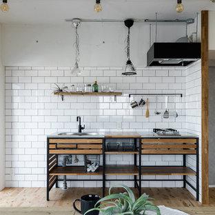 名古屋のインダストリアルスタイルのおしゃれなキッチン (一体型シンク、オープンシェルフ、ステンレスカウンター、白いキッチンパネル、サブウェイタイルのキッチンパネル、シルバーの調理設備、無垢フローリング) の写真