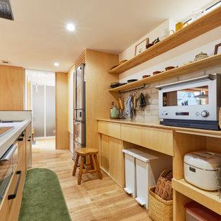 他の地域のアジアンスタイルのおしゃれなキッチン (フラットパネル扉のキャビネット、中間色木目調キャビネット、白いキッチンパネル、シルバーの調理設備、無垢フローリング、茶色い床、白いキッチンカウンター) の写真