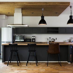На фото: параллельная кухня-гостиная в восточном стиле с фасадами с утопленной филенкой, черными фасадами, деревянной столешницей, паркетным полом среднего тона, островом и коричневым полом с