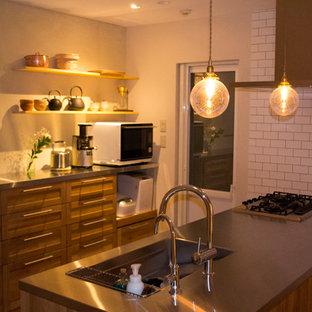 Offene, Zweizeilige Asiatische Küche mit hellbraunen Holzschränken, Edelstahl-Arbeitsplatte, Küchenrückwand in Braun, Rückwand aus Holz, bunten Elektrogeräten, Terrakottaboden, Kücheninsel und braunem Boden in Kobe