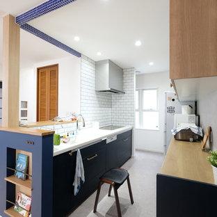 他の地域のコンテンポラリースタイルのおしゃれなキッチン (フラットパネル扉のキャビネット、青いキャビネット、木材カウンター、白いキッチンパネル、サブウェイタイルのキッチンパネル、シルバーの調理設備の、グレーの床、茶色いキッチンカウンター) の写真