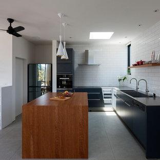 東京23区のモダンスタイルのおしゃれなキッチン (一体型シンク、フラットパネル扉のキャビネット、黒いキャビネット、白いキッチンパネル、セラミックタイルのキッチンパネル、黒い調理設備、グレーの床) の写真