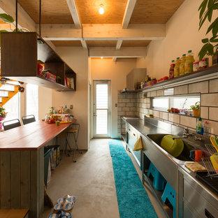 他の地域のインダストリアルスタイルのおしゃれなキッチン (シングルシンク、フラットパネル扉のキャビネット、ステンレスキャビネット、ステンレスカウンター、白いキッチンパネル) の写真