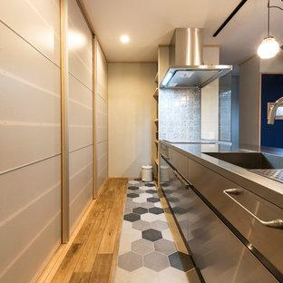 福岡のミッドセンチュリースタイルのおしゃれなI型キッチン (シングルシンク、フラットパネル扉のキャビネット、ステンレスキャビネット、ステンレスカウンター、無垢フローリング、茶色い床) の写真