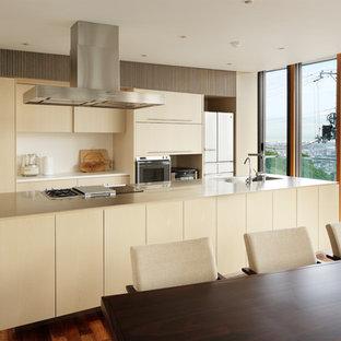 大阪のモダンスタイルのおしゃれなキッチン (一体型シンク、フラットパネル扉のキャビネット、白いキャビネット、クオーツストーンカウンター、黒い調理設備、無垢フローリング、茶色い床、ベージュのキッチンカウンター) の写真