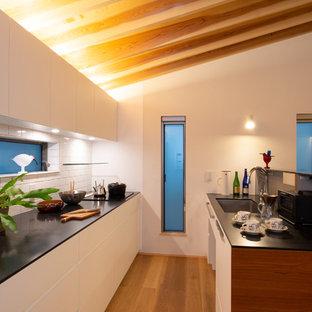 他の地域のコンテンポラリースタイルのおしゃれなキッチン (アンダーカウンターシンク、フラットパネル扉のキャビネット、白いキャビネット、人工大理石カウンター、白いキッチンパネル、パネルと同色の調理設備、無垢フローリング、茶色い床、黒いキッチンカウンター) の写真