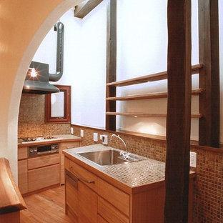神戸のアジアンスタイルのおしゃれなキッチン (ドロップインシンク、タイルカウンター、シルバーの調理設備の、茶色い床、フラットパネル扉のキャビネット、中間色木目調キャビネット、無垢フローリング) の写真