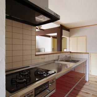 他の地域のアジアンスタイルのおしゃれなキッチン (一体型シンク、インセット扉のキャビネット、赤いキャビネット、ステンレスカウンター、白いキッチンパネル、セラミックタイルのキッチンパネル、シルバーの調理設備の、淡色無垢フローリング、アイランドなし) の写真