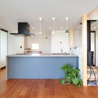 他の地域のコンテンポラリースタイルのおしゃれなキッチン (茶色い床、白いキッチンカウンター) の写真