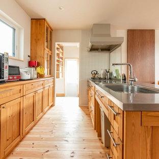 他の地域のカントリー風おしゃれなキッチン (シングルシンク、落し込みパネル扉のキャビネット、中間色木目調キャビネット、ステンレスカウンター、淡色無垢フローリング、ベージュの床、茶色いキッチンカウンター) の写真
