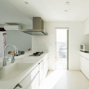 Modern inredning av ett stort linjärt kök med öppen planlösning, med en integrerad diskho, luckor med profilerade fronter, vita skåp, laminatbänkskiva, vitt stänkskydd, stänkskydd i keramik, vita vitvaror, plywoodgolv, en köksö och vitt golv