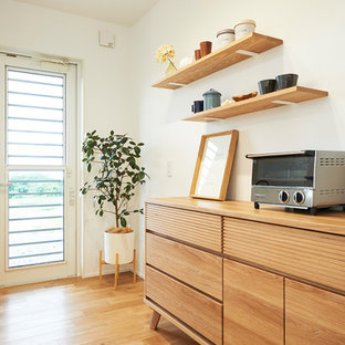Mid-sized scandinavian single-wall open plan kitchen in Other with an integrated sink, beaded inset cabinets, light wood cabinets, solid surface benchtops, white splashback, light hardwood floors, no island, multi-coloured floor and white benchtop.