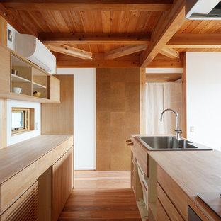 他の地域のアジアンスタイルのおしゃれなアイランドキッチン (シングルシンク、フラットパネル扉のキャビネット、中間色木目調キャビネット、木材カウンター、無垢フローリング、茶色い床) の写真