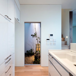 Small modern enclosed kitchen remodeling - Small minimalist galley plywood floor enclosed kitchen photo in Osaka with open cabinets, white cabinets, solid surface countertops, white backsplash, stainless steel appliances and an island