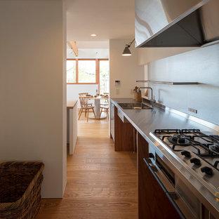大阪のモダンスタイルのおしゃれなキッチン (一体型シンク、フラットパネル扉のキャビネット、ステンレスカウンター、白いキッチンパネル、無垢フローリング、茶色い床) の写真