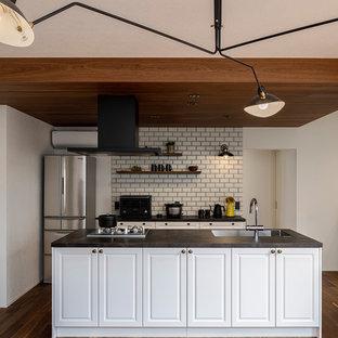 東京23区のインダストリアルスタイルのおしゃれなキッチン (アンダーカウンターシンク、インセット扉のキャビネット、白いキャビネット、黒い調理設備、無垢フローリング、茶色い床、黒いキッチンカウンター) の写真