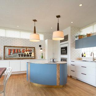 ビーチスタイルのおしゃれなキッチン (アンダーカウンターシンク、フラットパネル扉のキャビネット、青いキャビネット、白いキッチンパネル、シルバーの調理設備、淡色無垢フローリング、ベージュの床) の写真