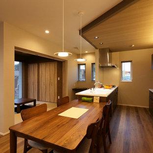 他の地域のコンテンポラリースタイルのおしゃれなアイランドキッチン (一体型シンク、フラットパネル扉のキャビネット、濃色木目調キャビネット、白いキッチンパネル、無垢フローリング、茶色い床) の写真