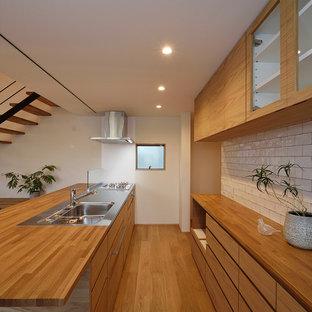 Zweizeilige Nordische Küche mit hellbraunen Holzschränken, Küchenrückwand in Weiß, braunem Boden, brauner Arbeitsplatte, Waschbecken, Edelstahl-Arbeitsplatte, braunem Holzboden und Halbinsel in Sonstige