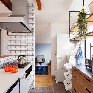 東京23区のエクレクティックスタイルのおしゃれなキッチン (フラットパネル扉のキャビネット、白いキャビネット、白いキッチンパネル、サブウェイタイルのキッチンパネル、テラコッタタイルの床、グレーの床、茶色いキッチンカウンター) の写真