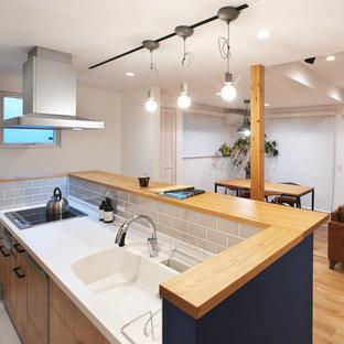 他の地域の広いカントリー風おしゃれなキッチン (フラットパネル扉のキャビネット、淡色木目調キャビネット、人工大理石カウンター、白い床、茶色いキッチンカウンター、淡色無垢フローリング) の写真